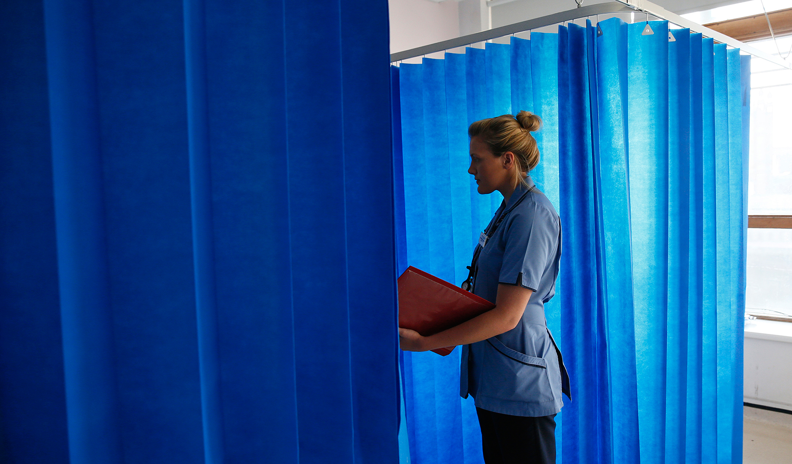 Health care worker talking to a patient behind a privacy curtain | Reuters/Stefan Wermuth