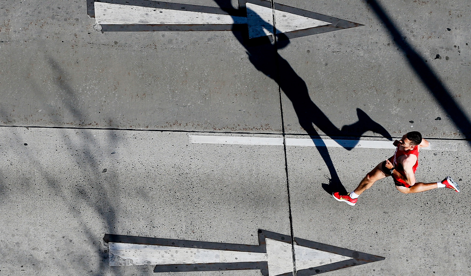 A runner going in the opposite direction of arrows on the road | Reuters/Leonhard Foeger