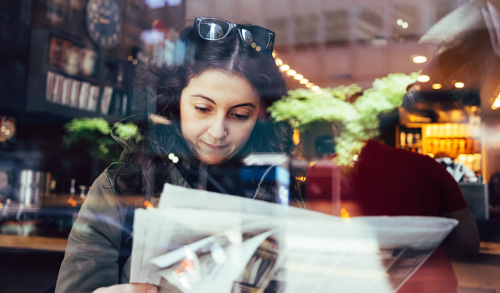 A woman reads a newspaper | iStock/FilippoBacci