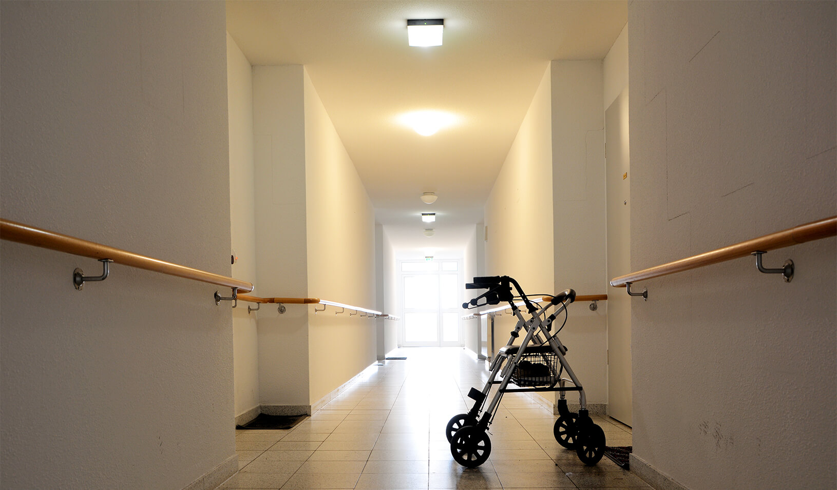 A walker is left behind in the empty hallway of an eldercare facility | iStock/Heiko Küverling