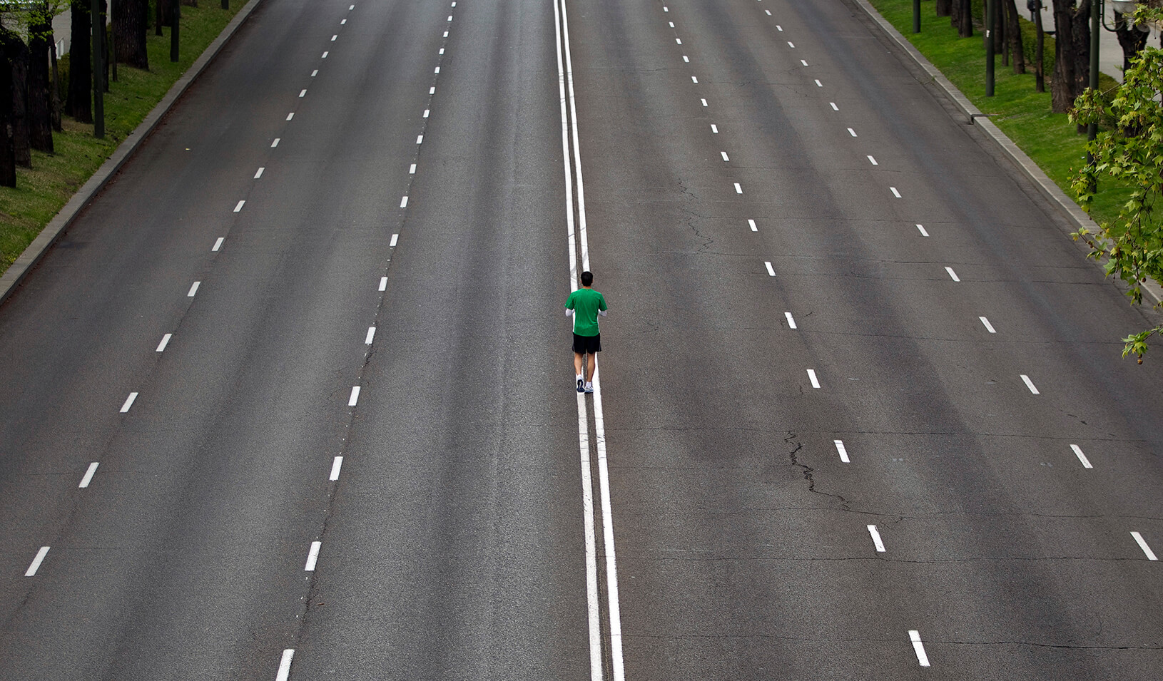 A man standing in the middle of an empty six-lane road | Reuters/Paul Hanna