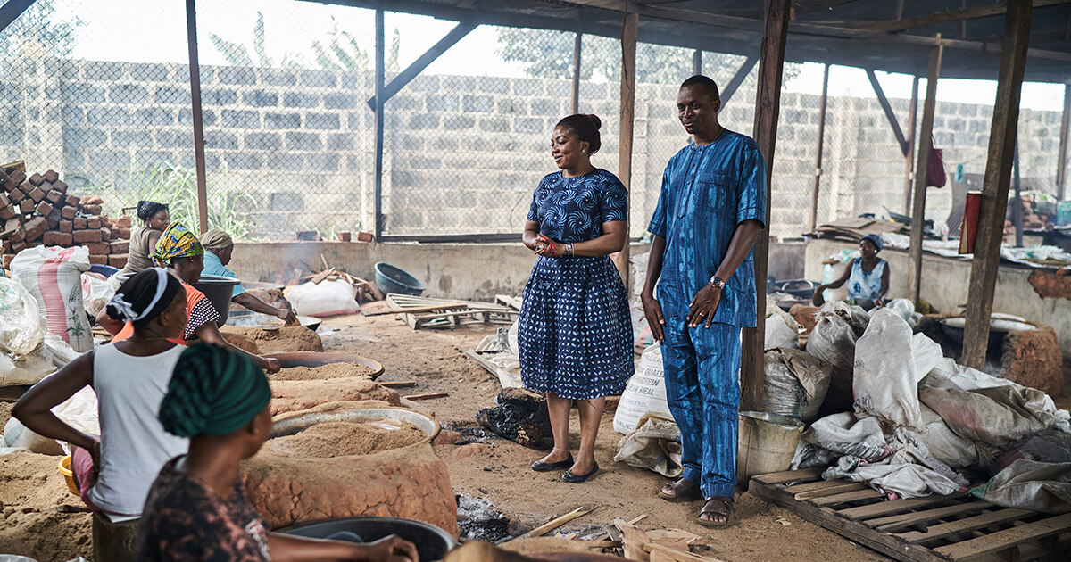 Workers drying spent brewery grain for poultry feed at Nation Feeders in Nigeria.
