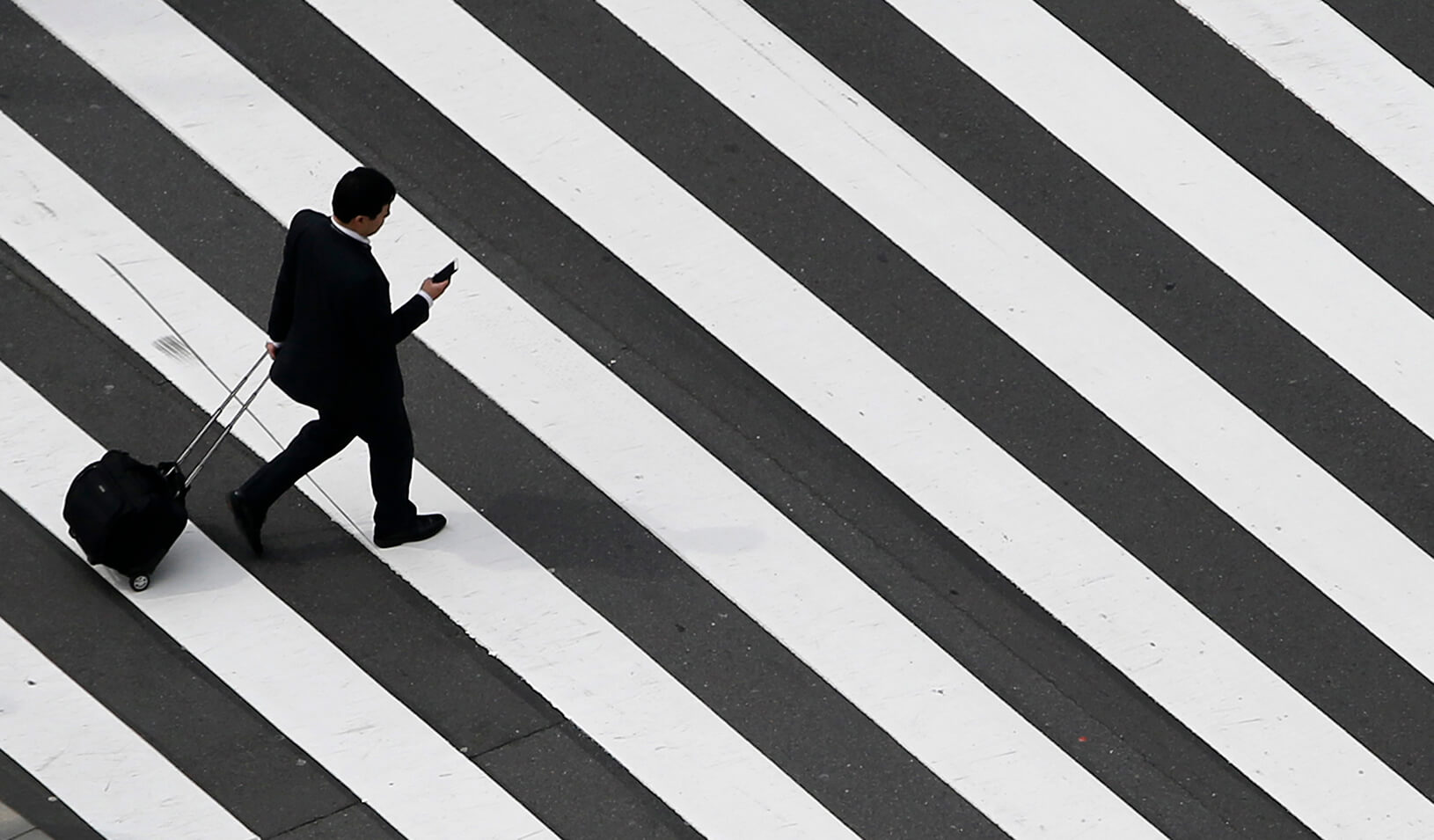 A businessman walks across the street, wheeling a bag. | Reuters/Yuya Shino
