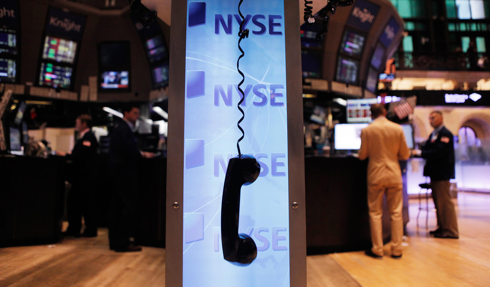 Telephone receiver hanging by its cord in front of the NYSE logo | Reuters/Lucas Jackson