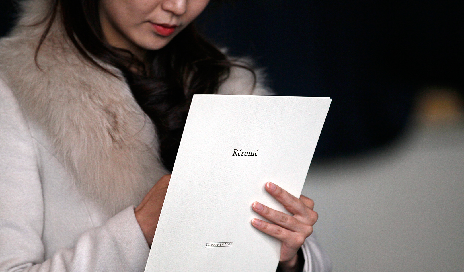 Woman holding resume folder while taking notes | Reuters/Rick Wilking