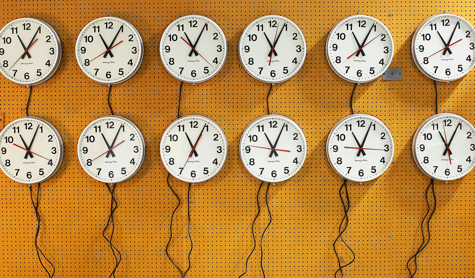 Twelve wall clocks close together. | Reuters/Brian Snyder
