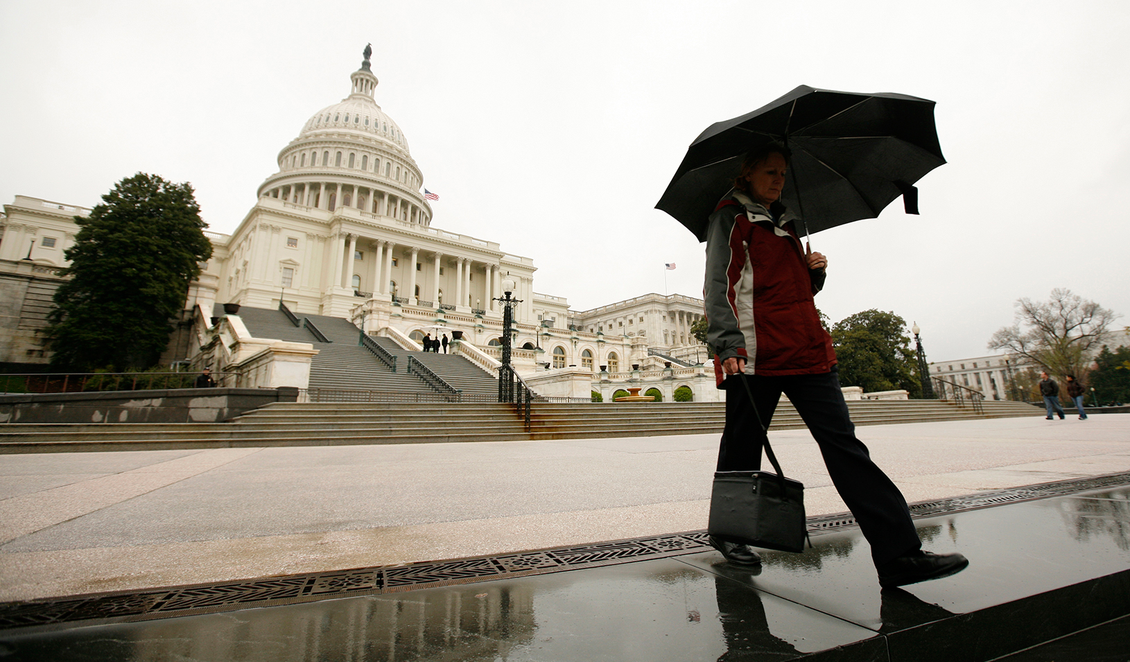 Man with an umbrella walking in front of the Capital