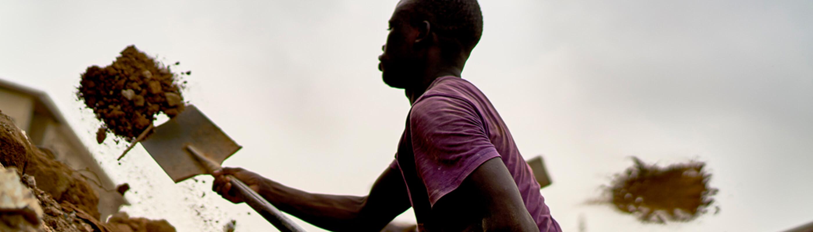 African man digging