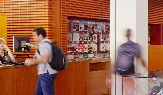 students walking past i-Desk in library