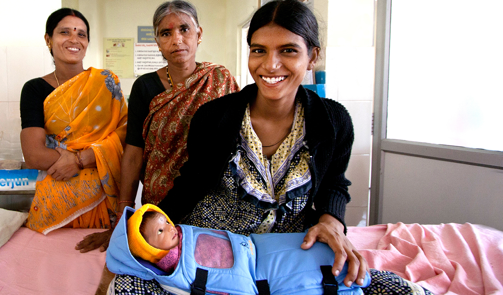 Three women near a baby wrapped in an Embrace warmer