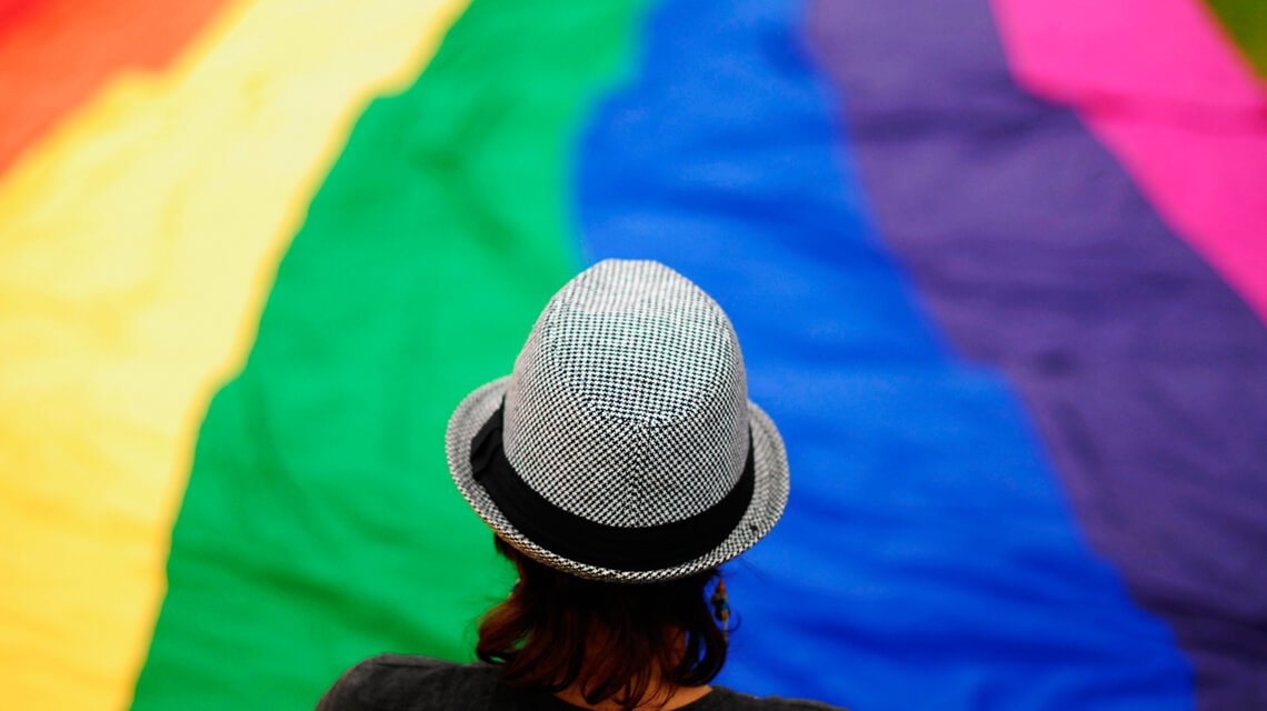 person standing in front of huge rainbow flag