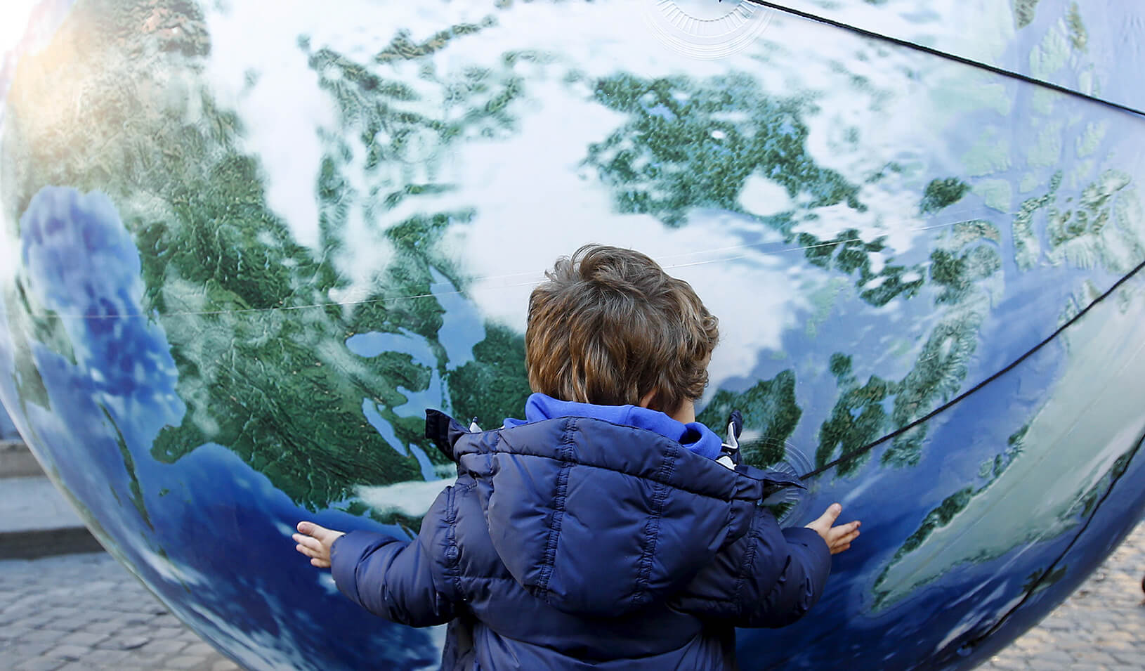 A child embraces a globe shaped balloon | Reuters/Alessandro Bianchi