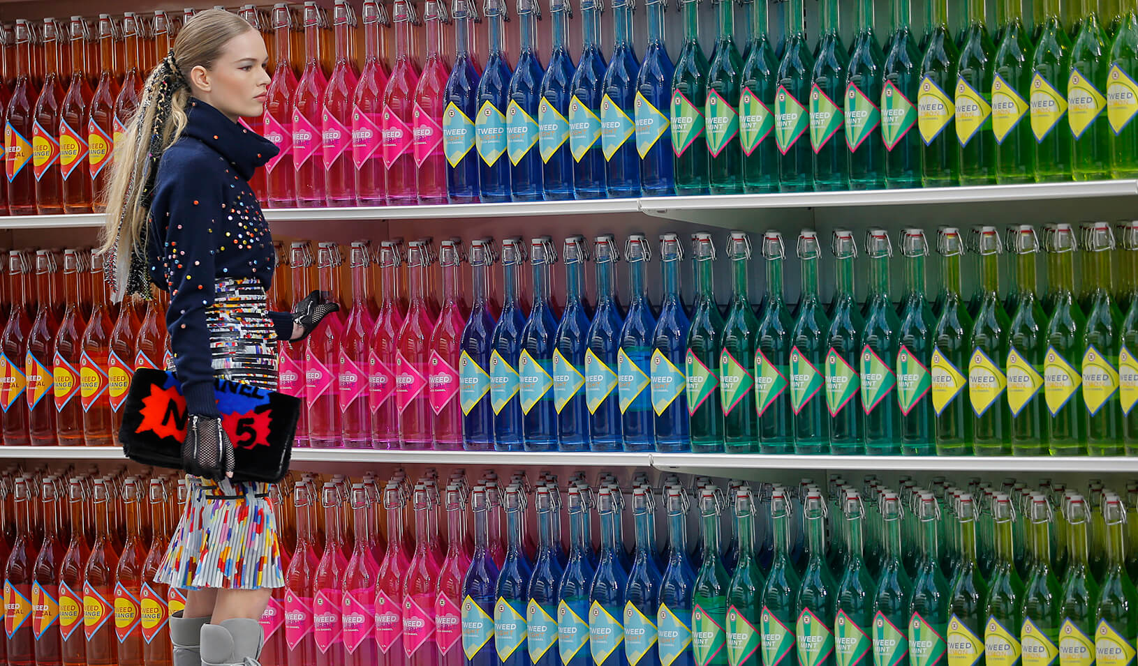 A woman stands in front of shelves of beverages | Reuters/Stephane Mahe