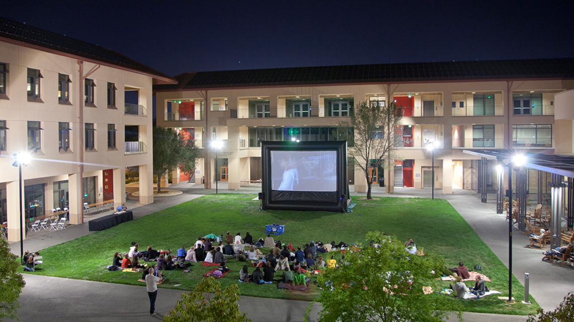 Students watching a movie in the Community Court at night