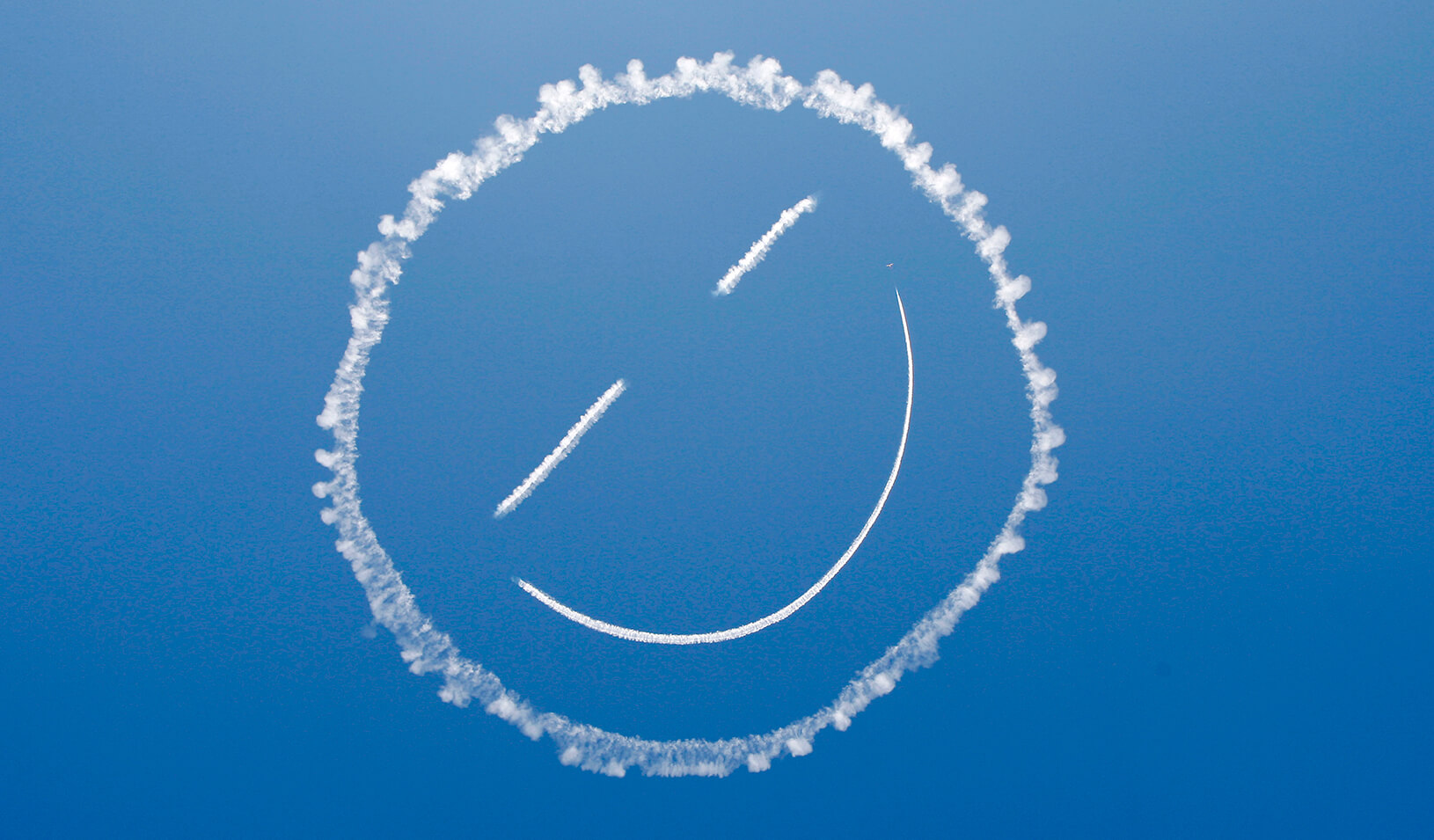 """A plane """"sky writes"""" a smiley face in the sky. 