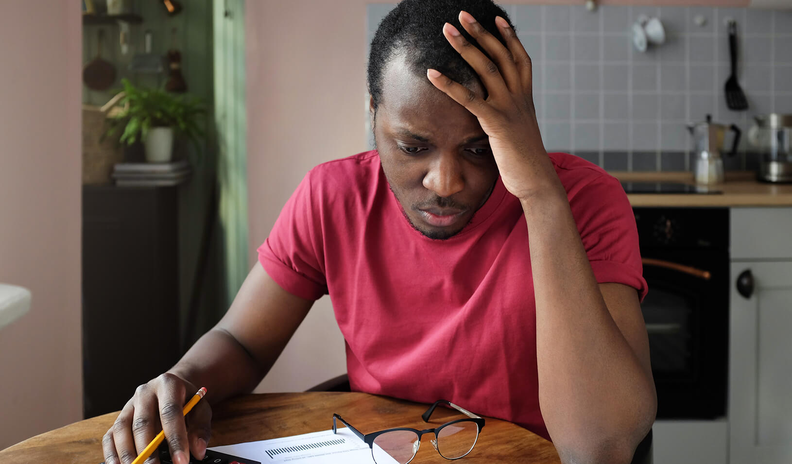 A young black man, anxious about his bills. Credit: iStock/Damir Khabirov