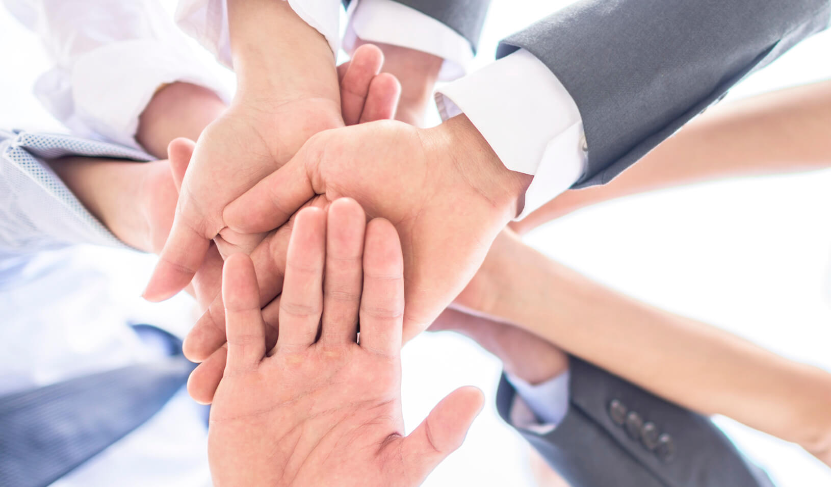 Six hands are clasped in friendship - all white | iStock/andresr