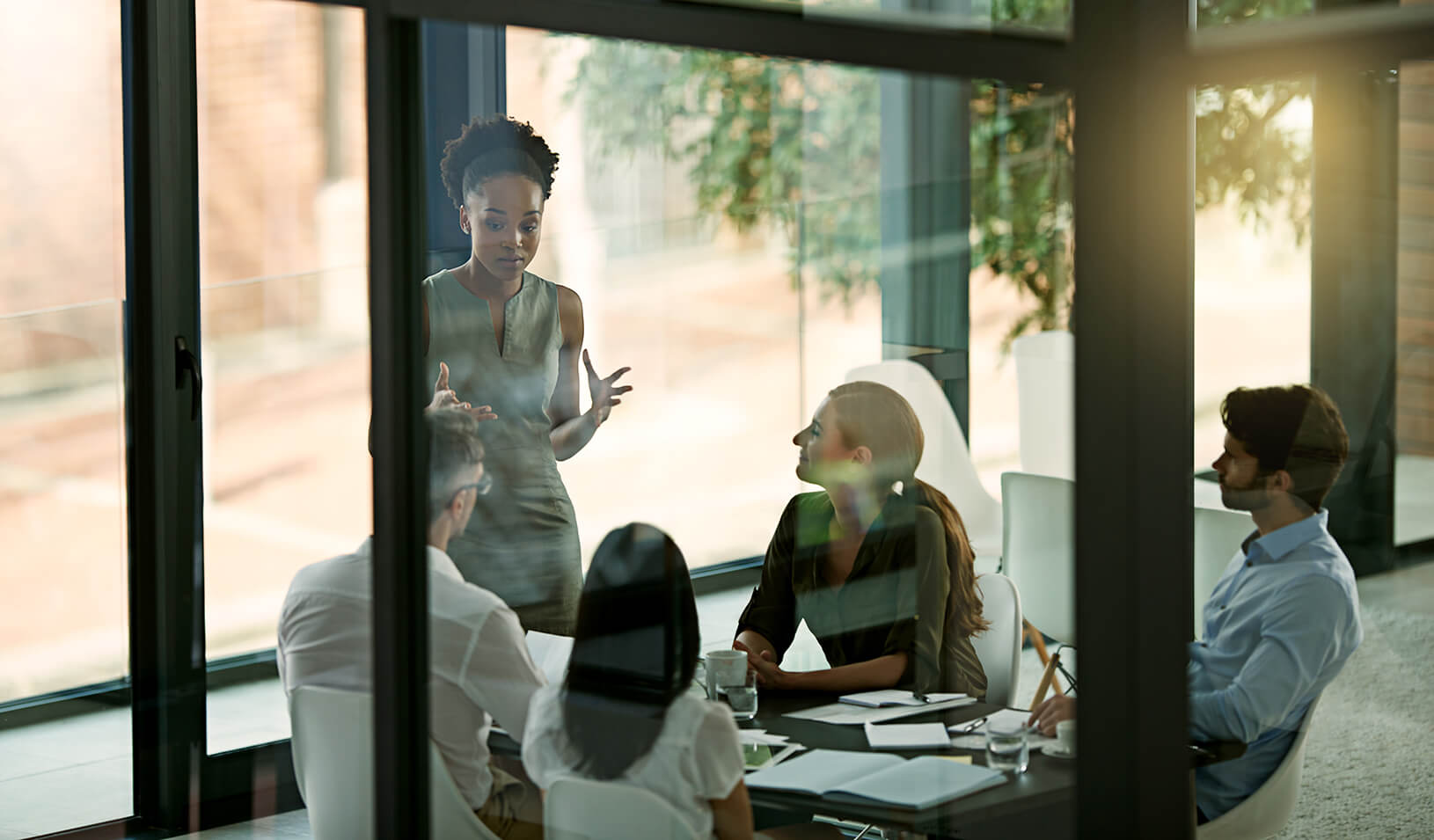 A group of people talking at a conference table | iStock/Peopleimages