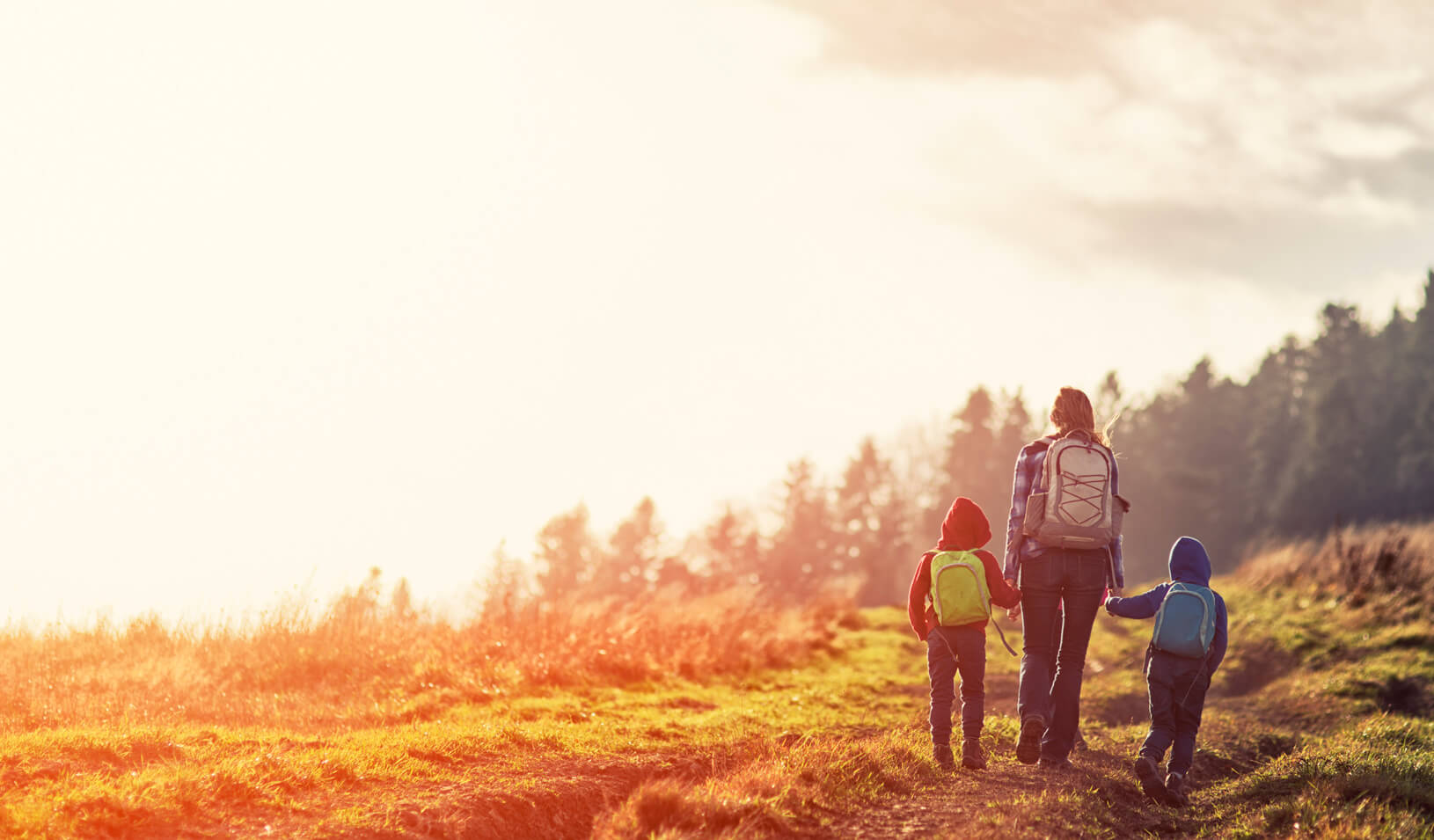 A woman hiking with her children|iStock/Imgorthand