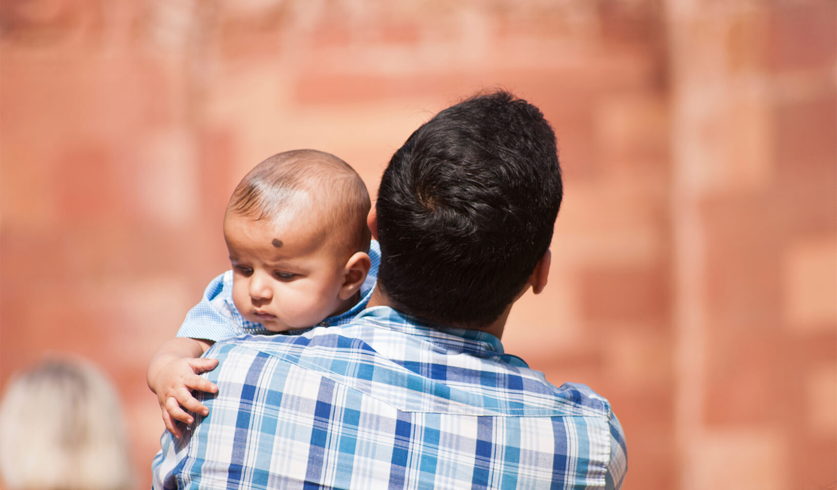 A father holding a baby | iStock/RobertoMussi