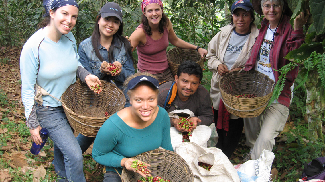 Students with workers and coffee beans during study trip to Guatemala