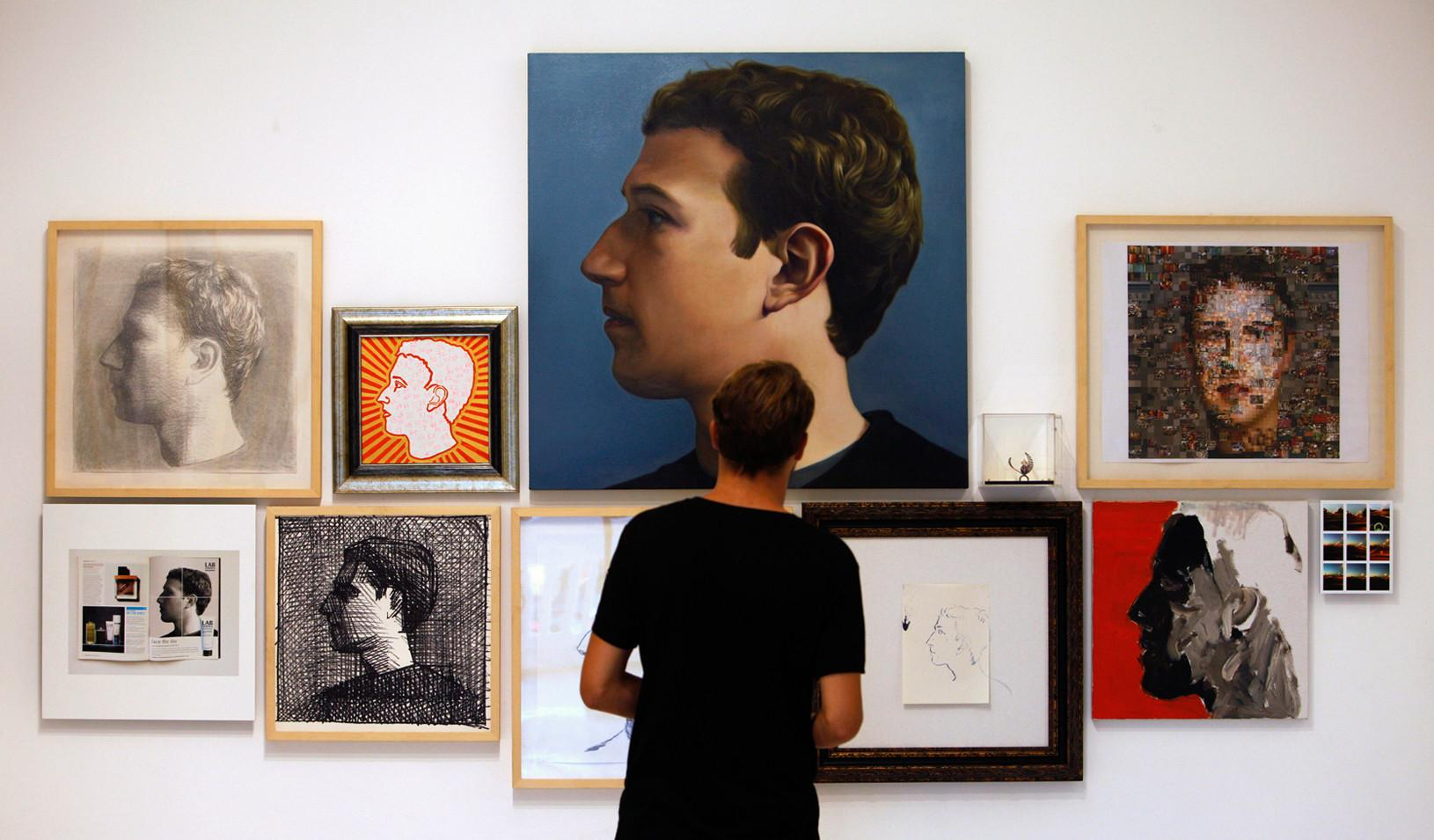 Portraits of Mark Zuckerberg hanging on a wall.