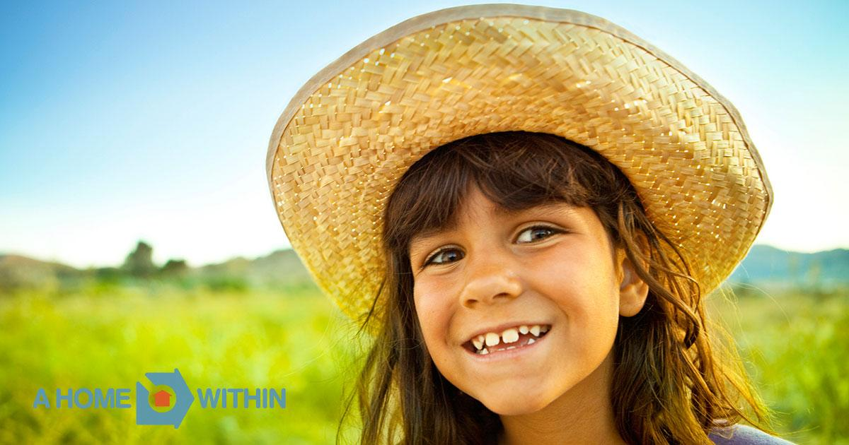 A beaming young girl in straw hat.