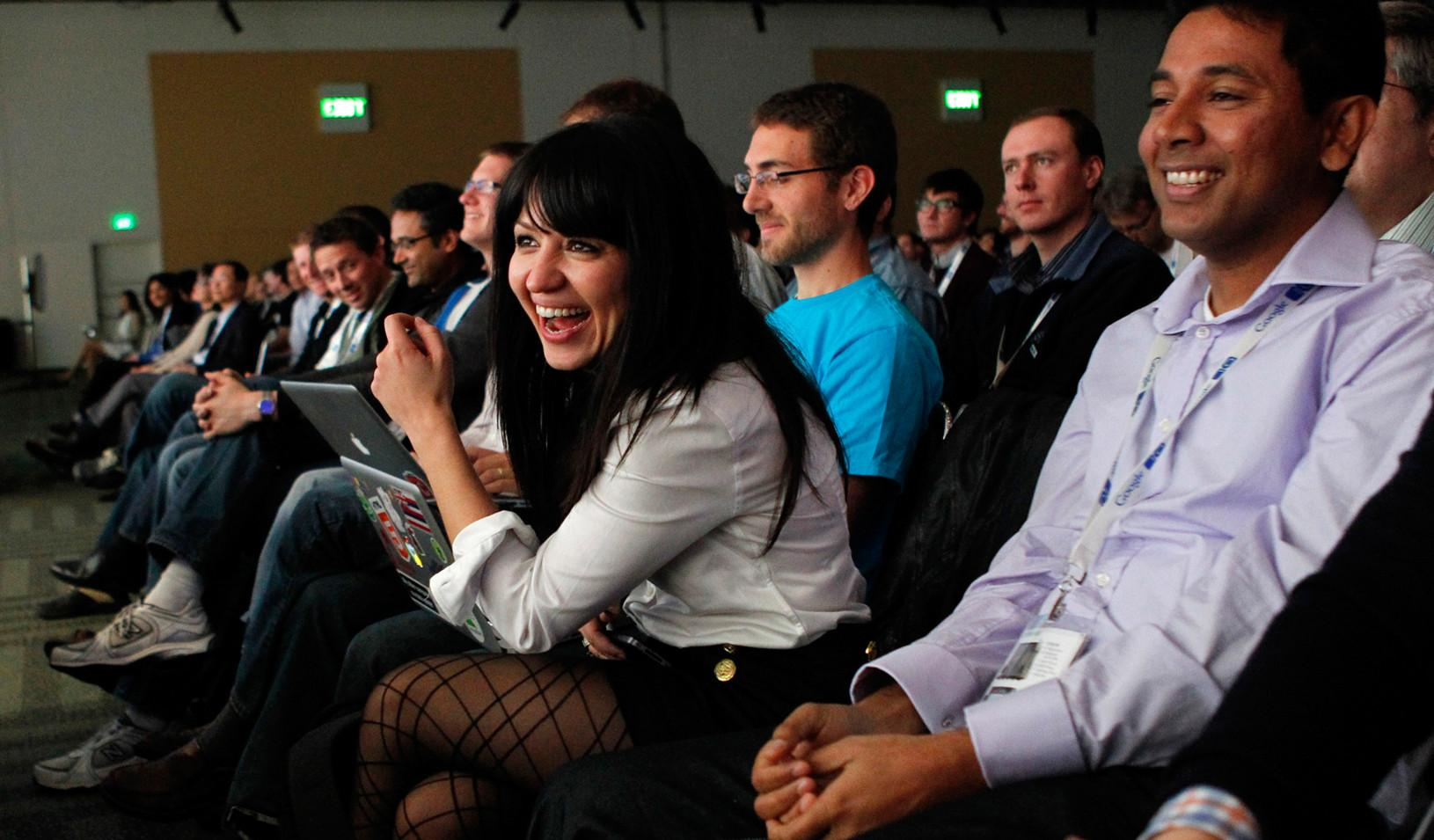 Woman leaning forward and laughing while listening to a presentation
