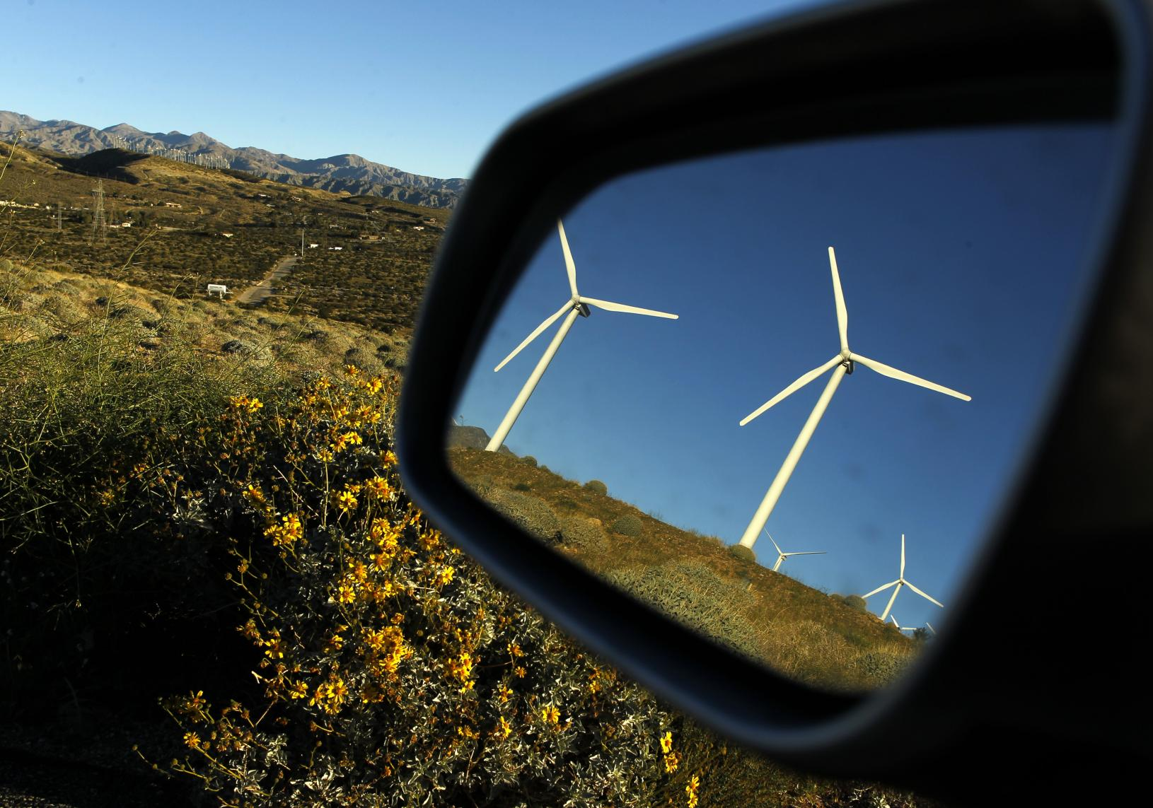 Windmills are reflected in a car mirror at a wind farm.