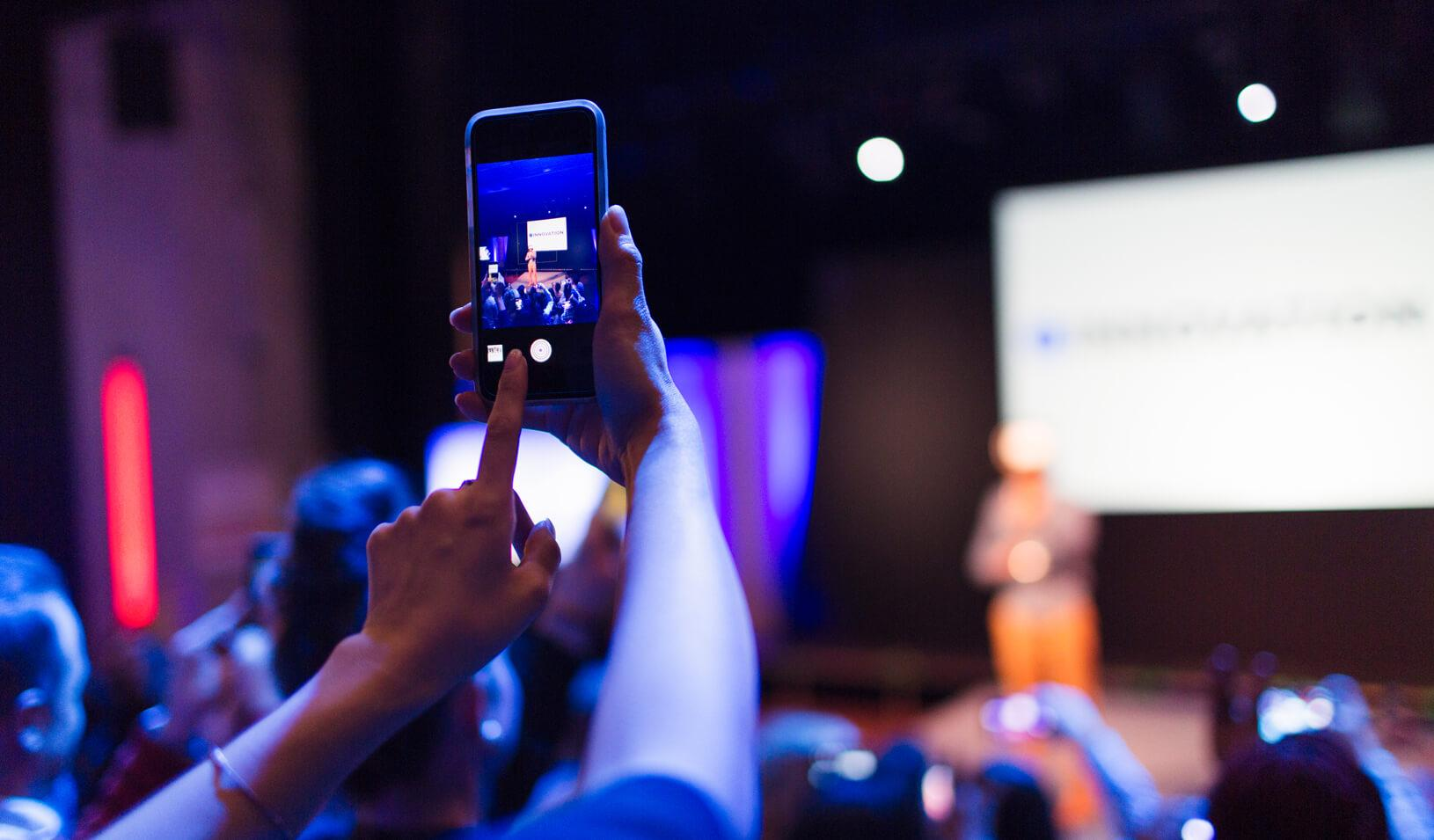 An audience member takes a photo of someone presenting on stage. Credit: iStock/Django