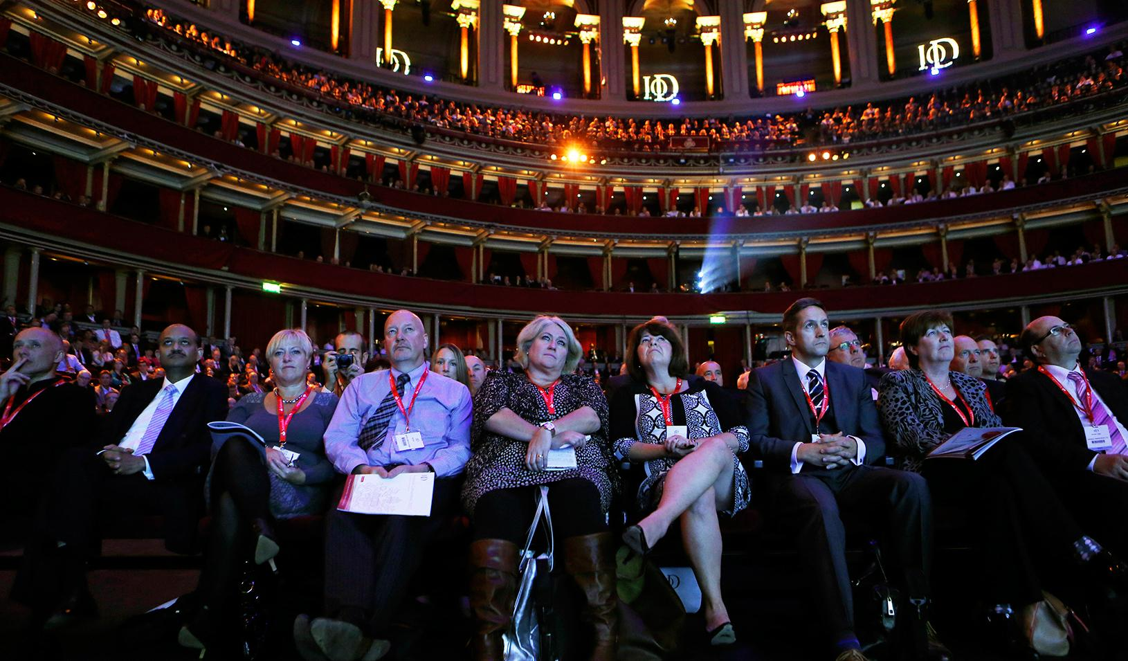 Members of the audience listen as Britain's Chancellor of the Exchequer George Osborne speaks at the Institute of Directors annual convention in London September 18, 2013.