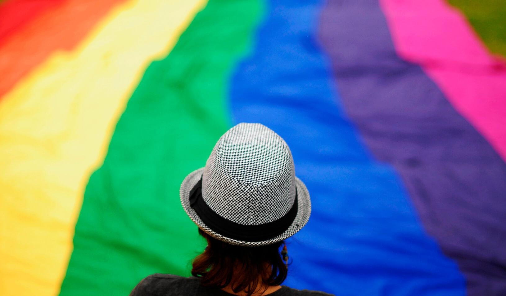 A transgender person overlooks a large rainbow banner