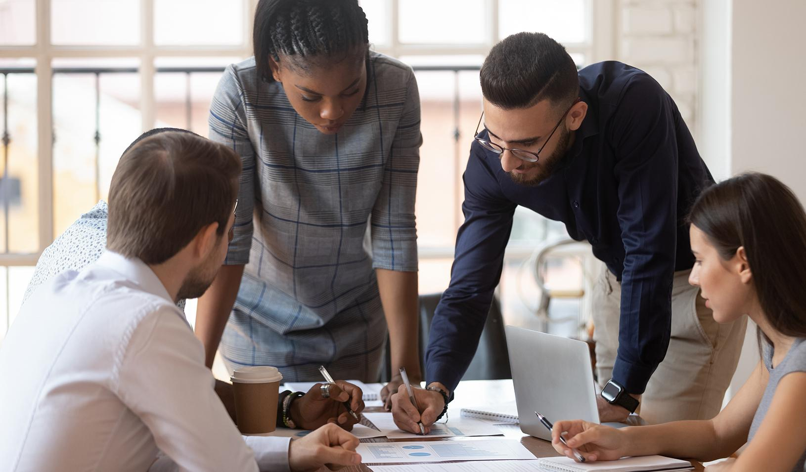Corporate business team brainstorming at an office table. Credit: iStock/Fizkes