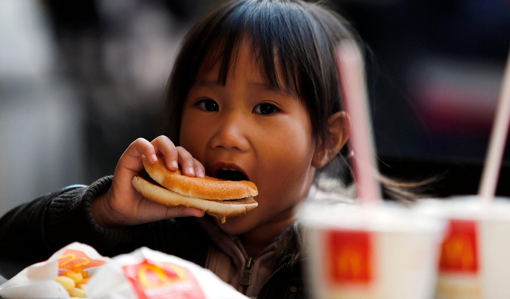 A child eats a hamburger at a fast food restaurant. | Reuters/Stefano Rellandini