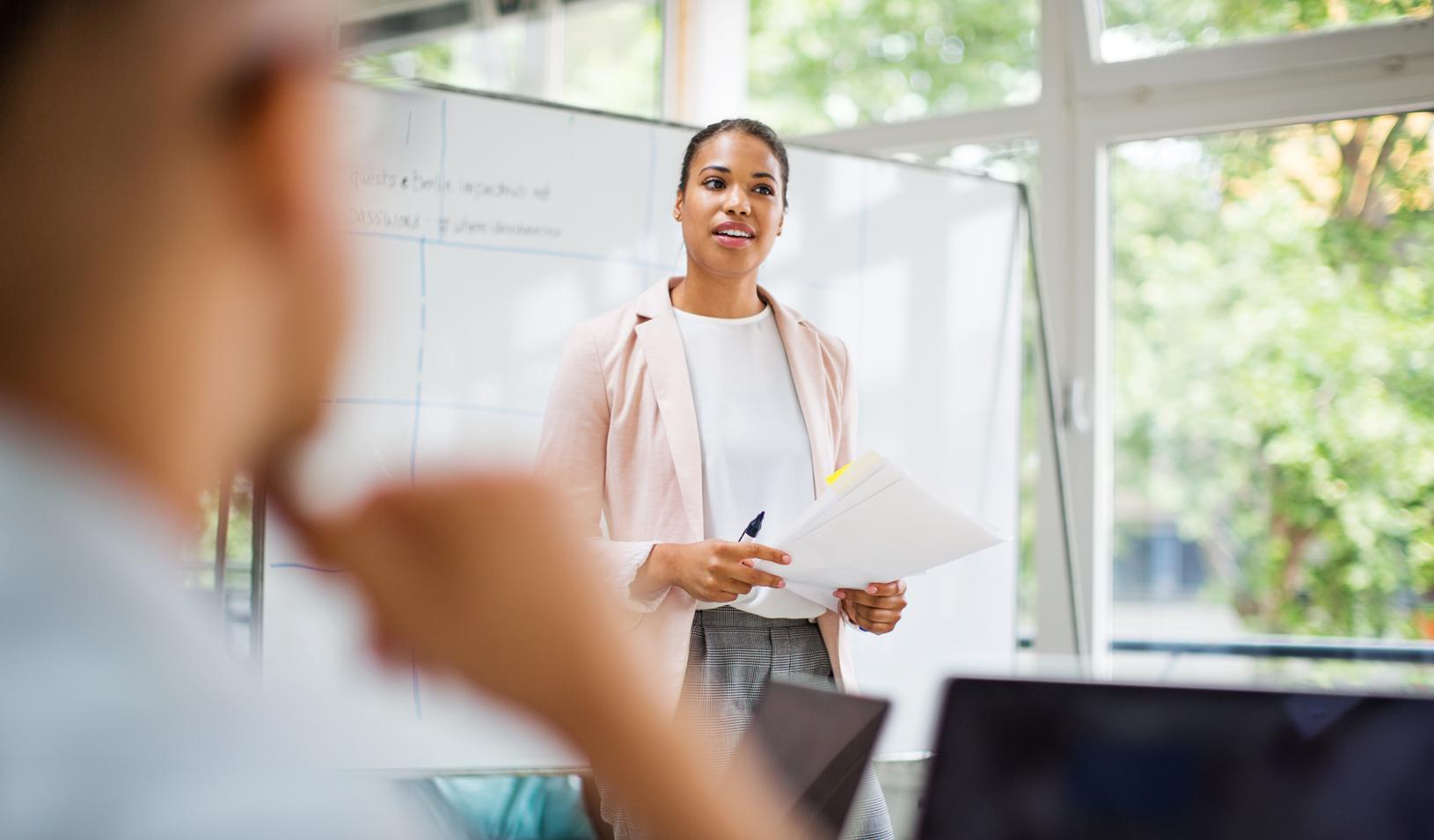 A photo of a woman presenting to her colleagues. Credit: iStock/alvarez