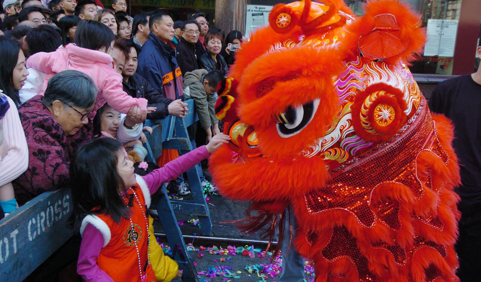 Children reach to touch the dragons taking part in Lunar New Year celebrations in New York's Chinatown section. It is believed that feeding the dragon a lucky red envelope, or patting it on the head, brings good fortune. Credit: Reuters/Henny Ray Adams