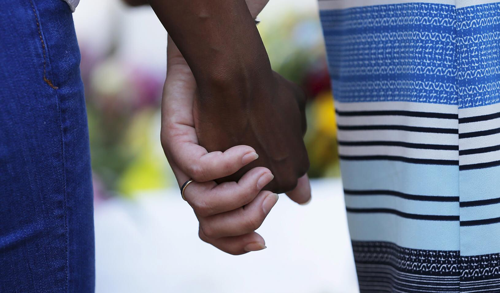 An African American and white person holding hands