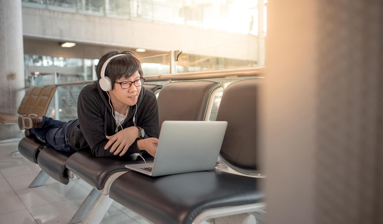 man watching a video on his laptop | iStock/Zephyr18