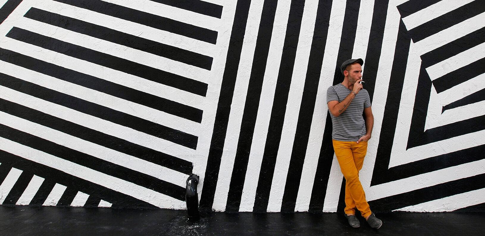 man smoking in front of an art mural