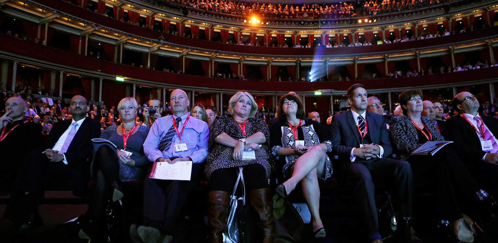 a seated crowd listening to a presenter