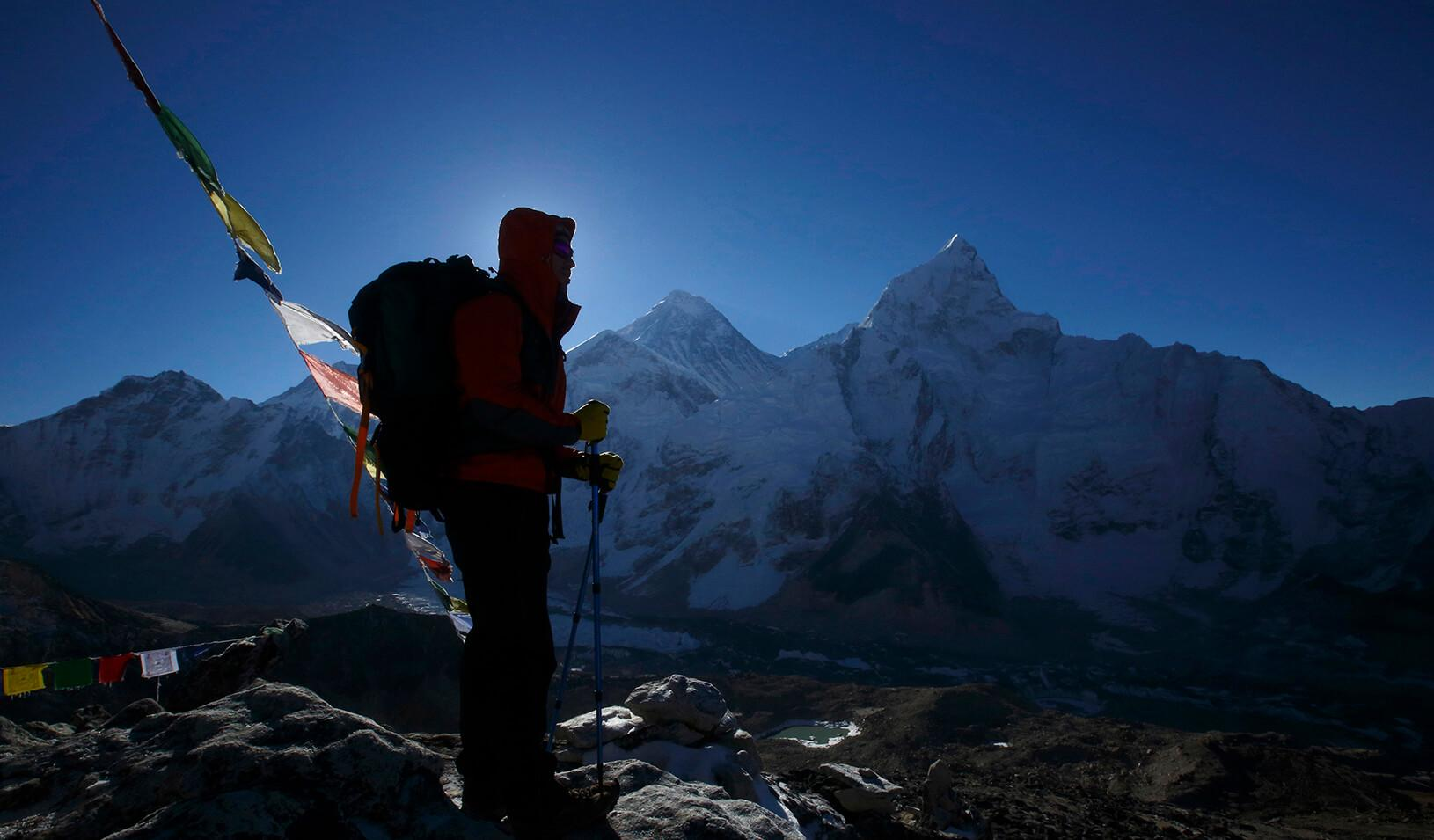 A trekker stands in front of Mount Everest