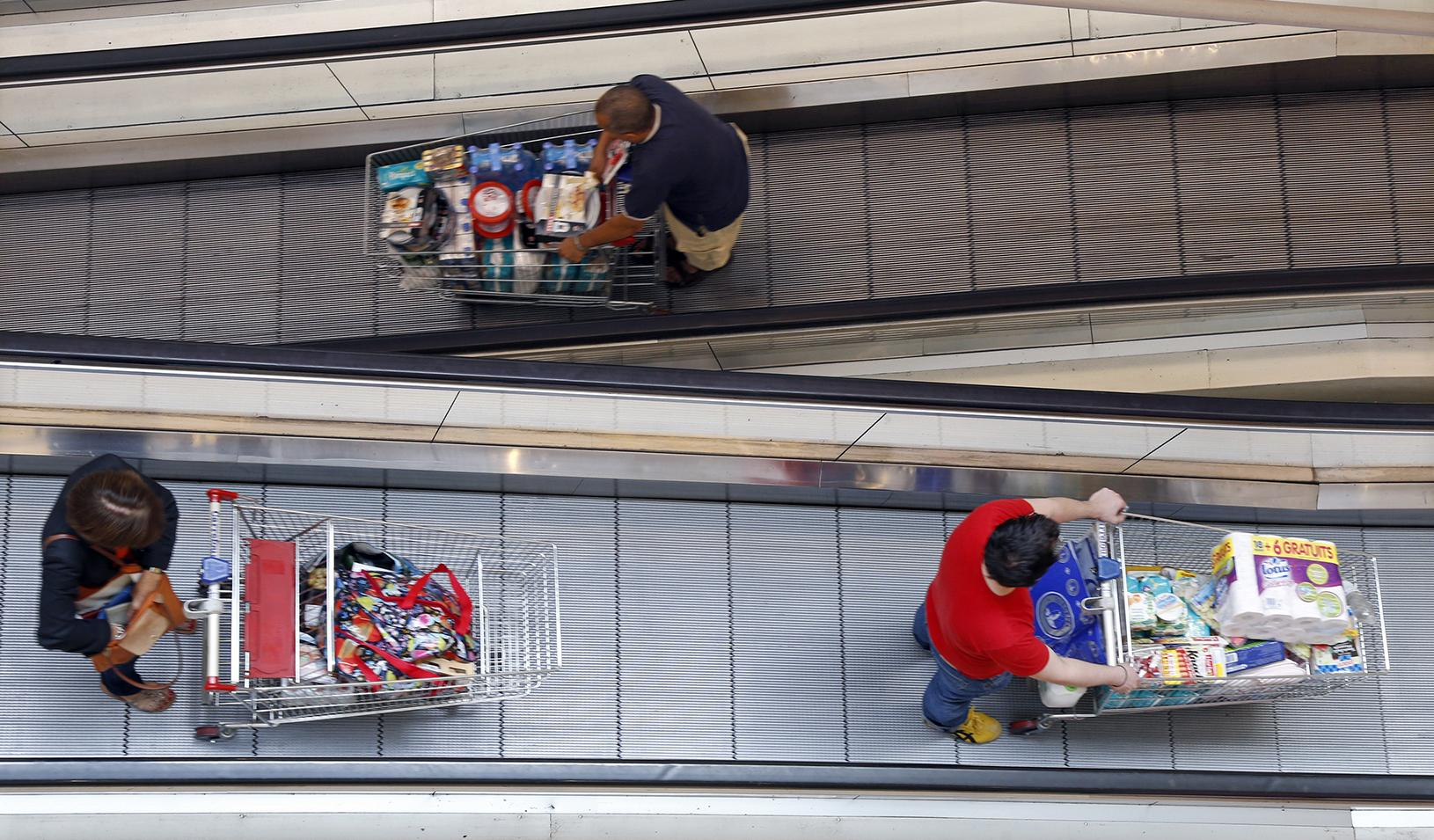 Customers push shopping carts on an escalator. Credit: Reuters/Charles Platiau