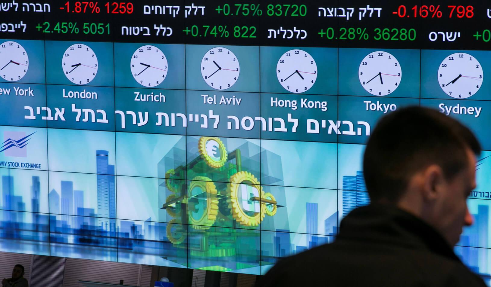 A man stands in front of an electronic board displaying market data at the Tel Aviv Stock Exchange, in Tel Aviv, Israel. | Reuters/Baz Ratner