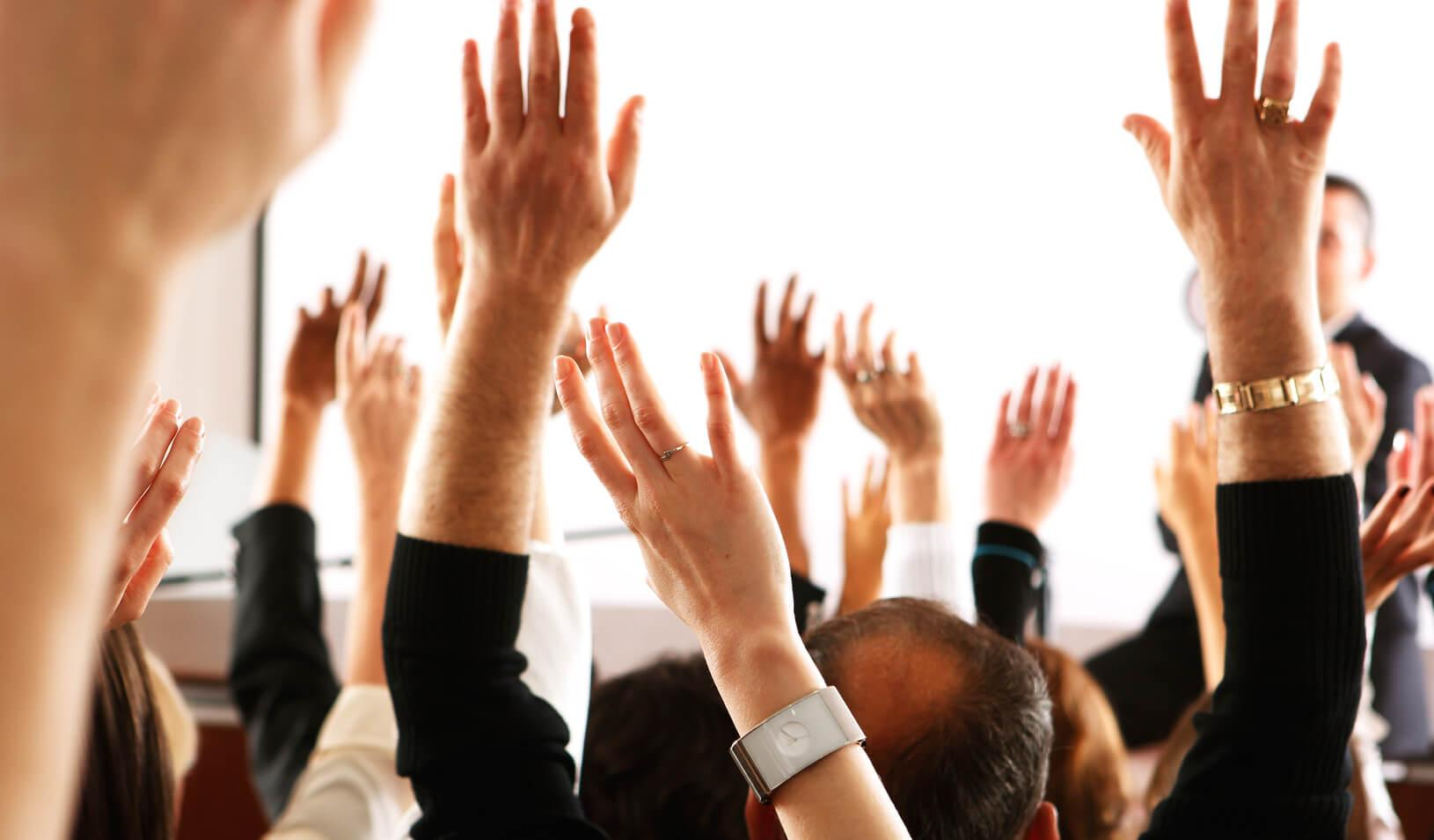 participants in an audience raising their hands