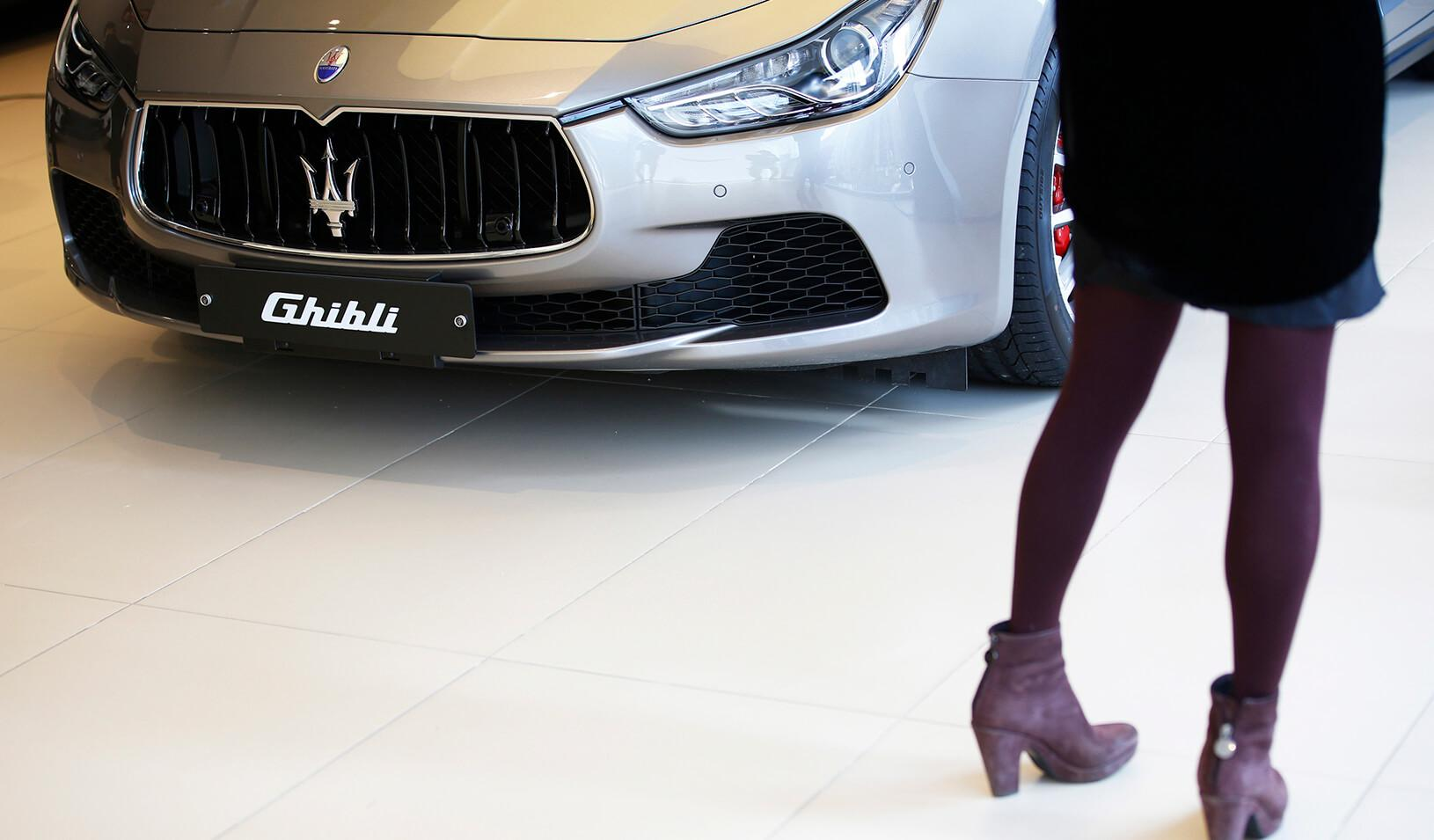 A woman looks at a Maserati Ghibli car at its dealership