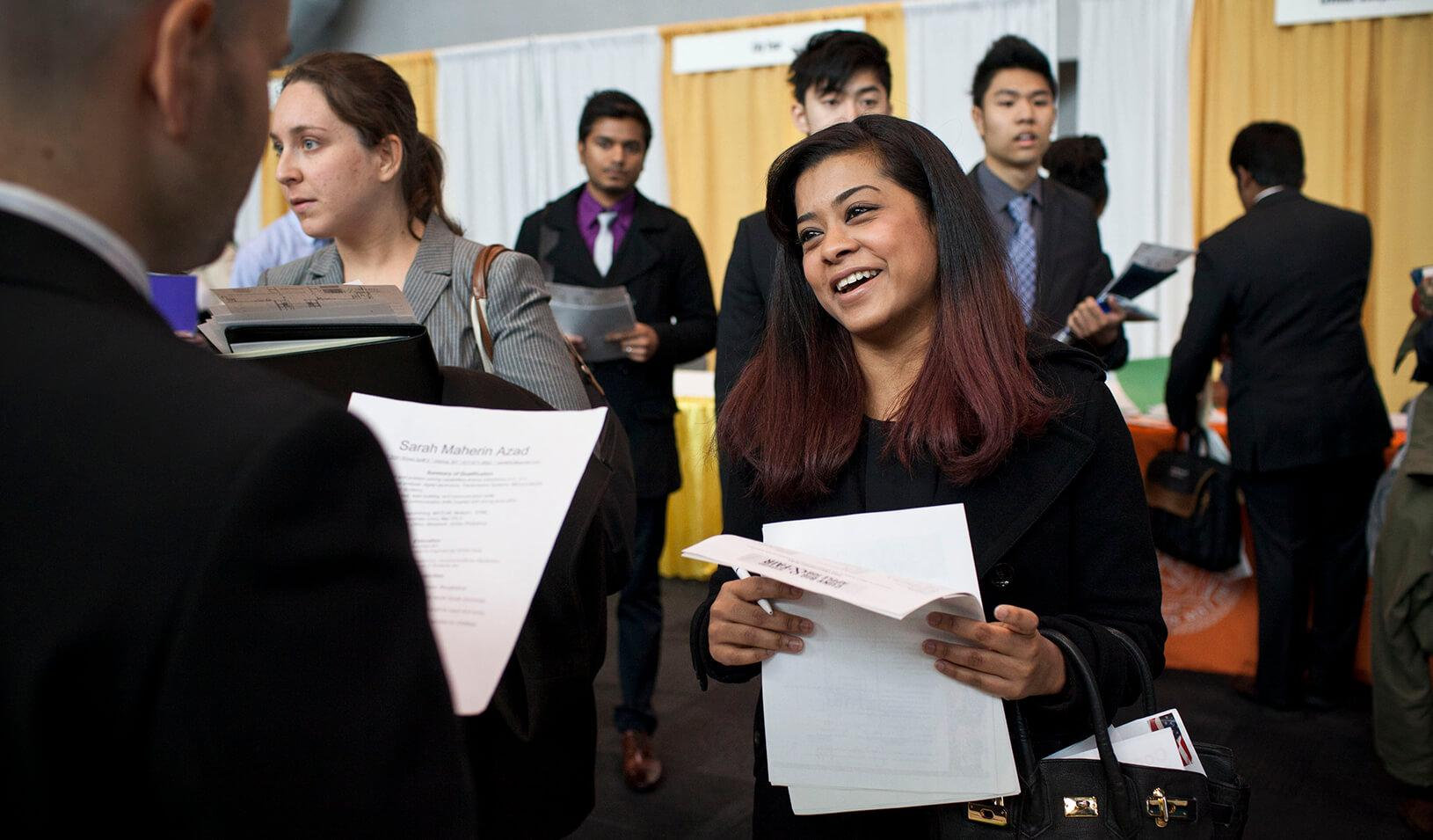 A female college senior meets a company representative at a job fair
