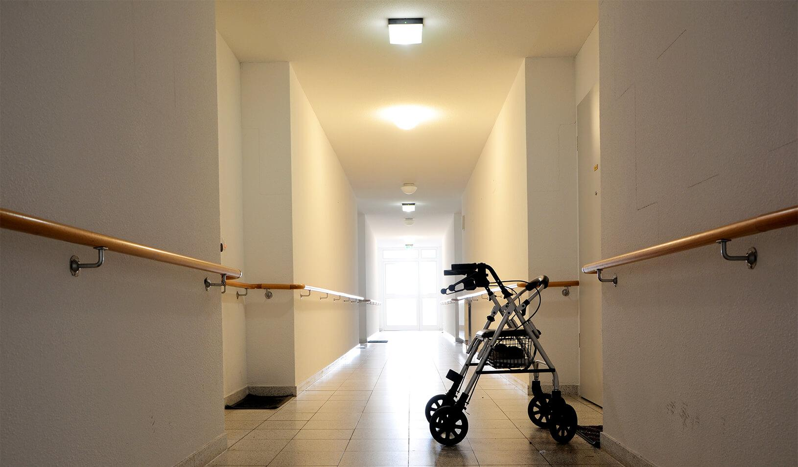 A walker is left behind in the empty hallway of an eldercare facility