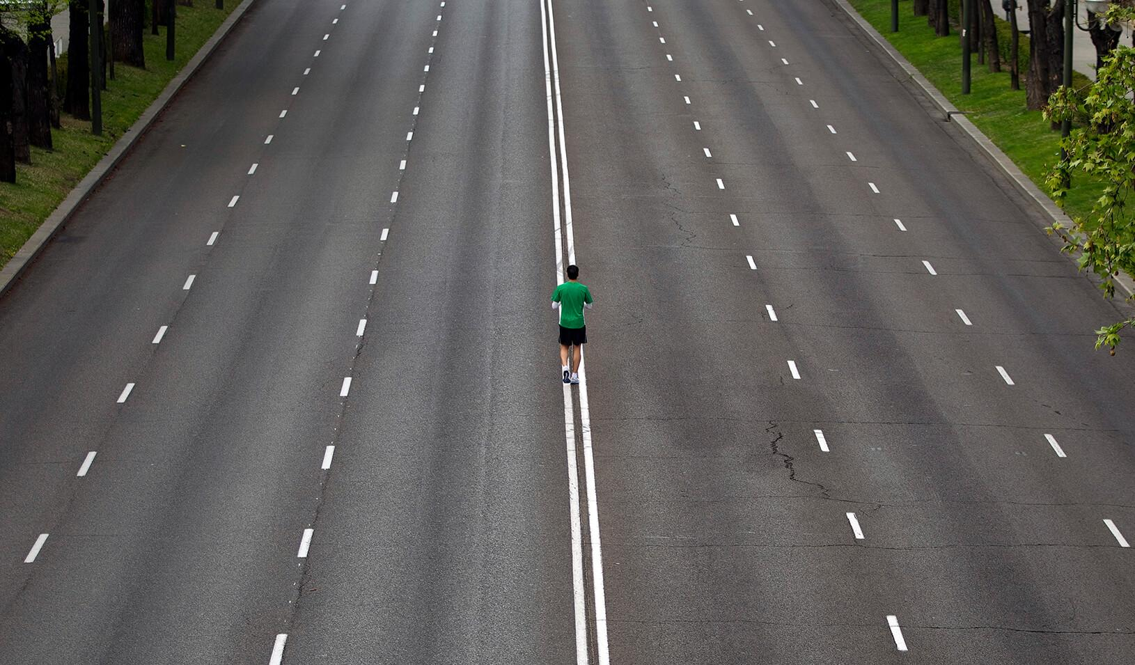 A man standing in the middle of an empty six-lane road