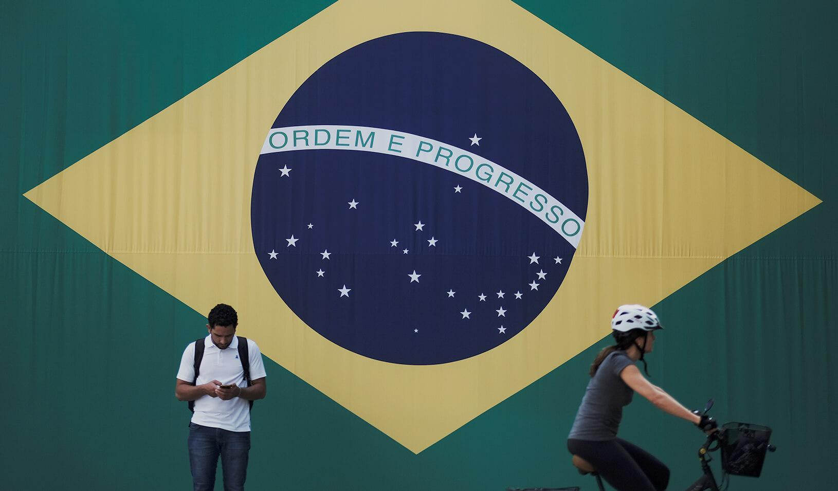 A man checks his mobile phone as a woman riding a bike passes next to a big Brazilian flag in Sao Paulo, Brazil. Credit: Reuters/Nacho Doce