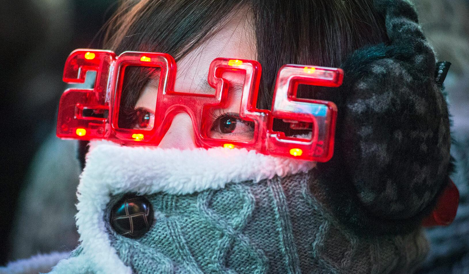 A woman wearing 2015 glasses during New Year's Eve celebrations